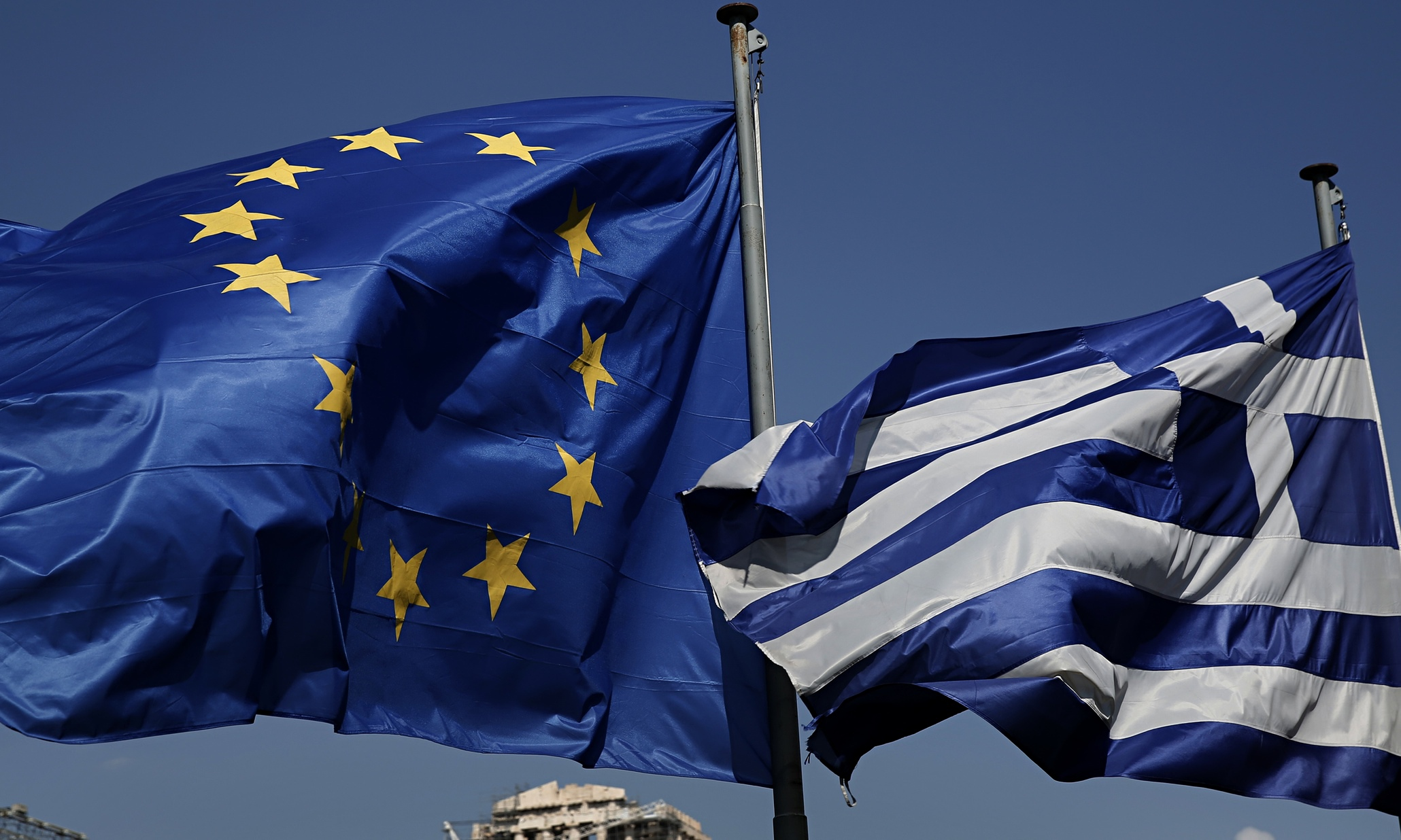 An EU and a Greek flag fly in front of the Parthenon